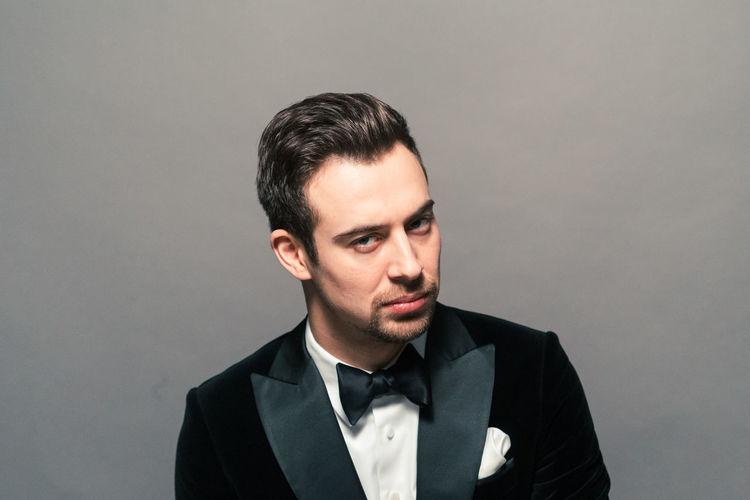Portrait of arrogant young man wearing tuxedo against gray background