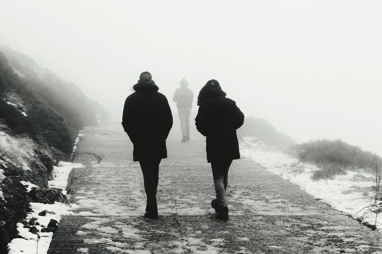 Rear view of silhouette people on road during winter