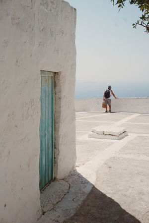 The tourist Nikia Nisiros Tourist View Architecture Beach Building Exterior Built Structure Day Full Length Greece Leisure Activity Lifestyles Nature Nisyros One Person Outdoors People Real People Sea Shadow Sky Standing Sunlight Young Adult