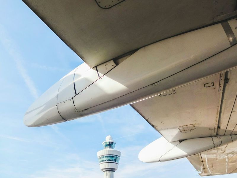 View from under the wing Low Angle View Sky Below No People Simplicity Schiphol Airport Schiphol Blue Control Tower Communications Tower Low Angle View Part Of Airplane Wing Airplane View AirPlane ✈
