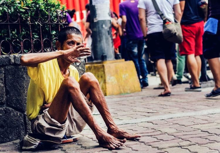 Full length of beggar hiding face while sitting on footpath