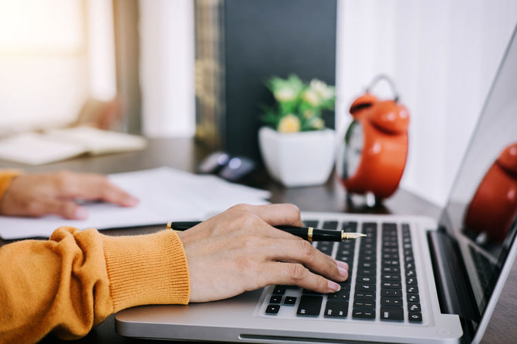 Cropped Hands Of Businesswoman Using Laptop At Desk
