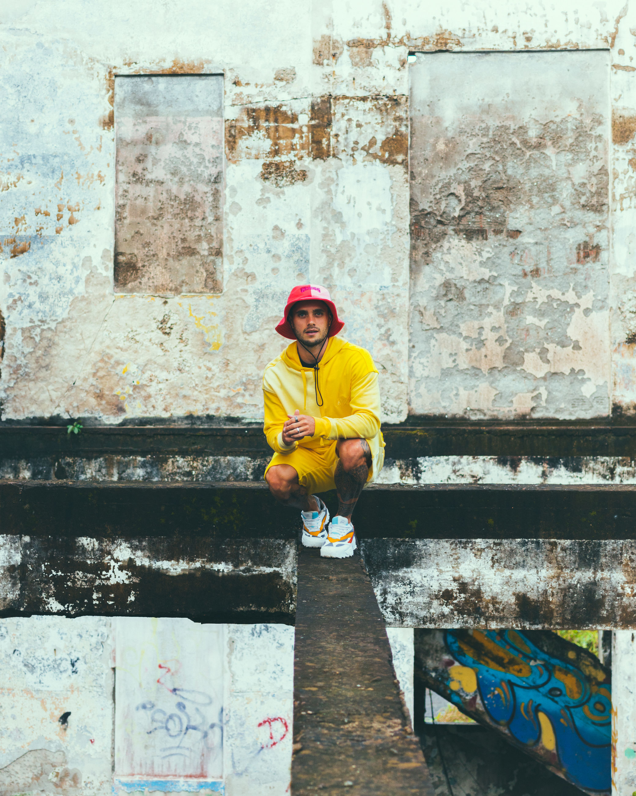 wall, one person, full length, art, architecture, yellow, adult, day, men, clothing, hat, helmet, built structure, front view, headwear, standing, occupation, wall - building feature, lifestyles, outdoors, young adult, hard hat, leisure activity, portrait, looking at camera, protection, person, casual clothing, building exterior, women, blue