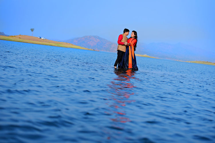 Tilt Shot Of Couple Standing On Shallow Water In Lake Against Sky