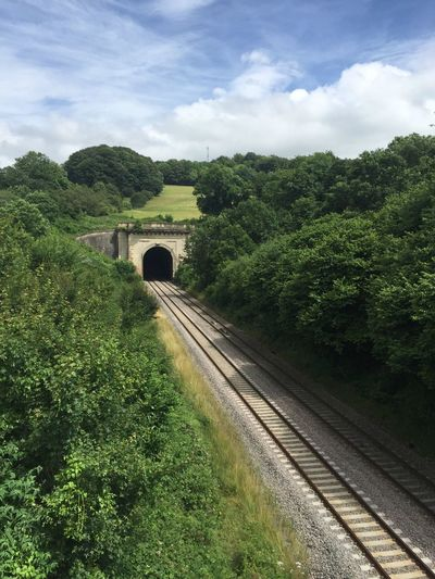 High Angle View Of Railroad Tracks Leading Towards Tunnel Amidst Trees Against Sky
