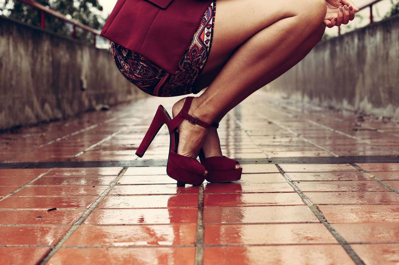 Low Section Of Woman With High Heels Crouching On Street
