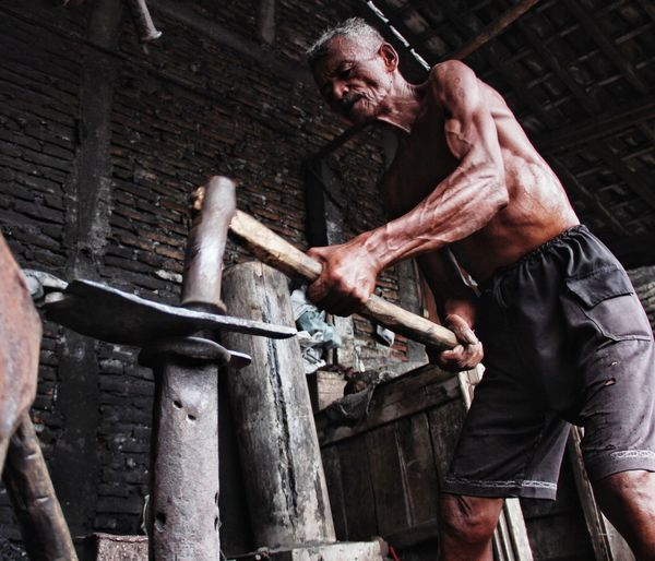 Low Angle View Of Shirtless Man Working With Hammer At Workshop