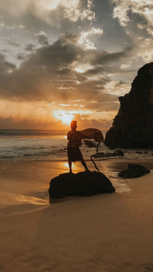 Silhouette man on rock at beach against sky during sunset