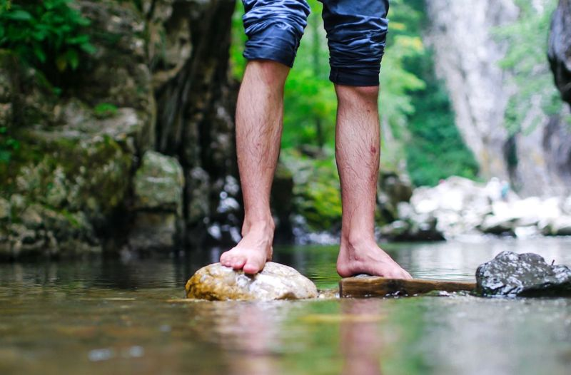 Low section of man standing on rock by stream