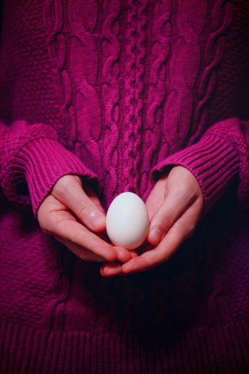 Midsection Of Woman Holding Egg