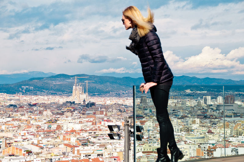 Young woman wearing warm clothing while standing on balcony against cityscape