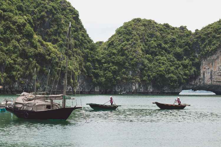 People sailing boats in sea against rock formations