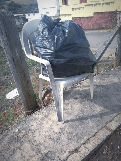 Chair Outdoors Day Low Section Trash Bag Trash Bag Street Sidewalk Houses Condominium Street Photography Some Kind Of Art Barbed Wire