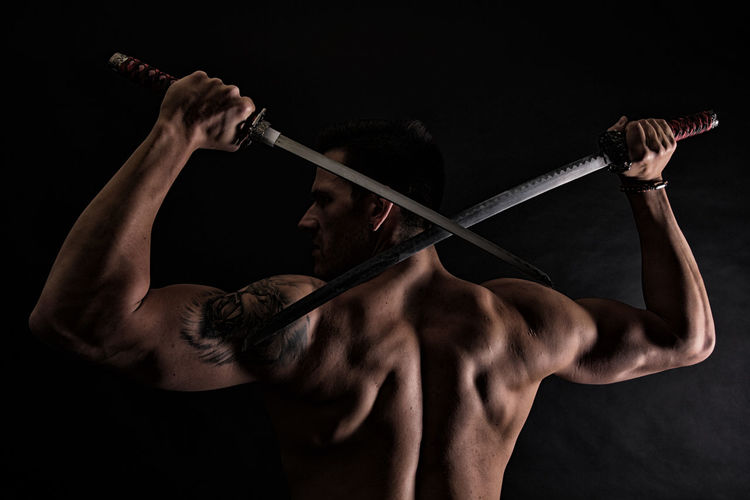 Rear view of shirtless muscular man holding katana swords against black background