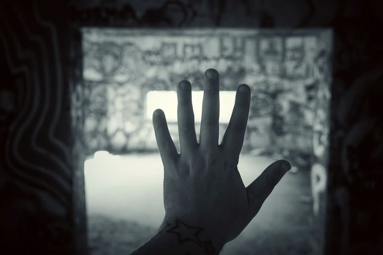 Close-up of human hand against wall