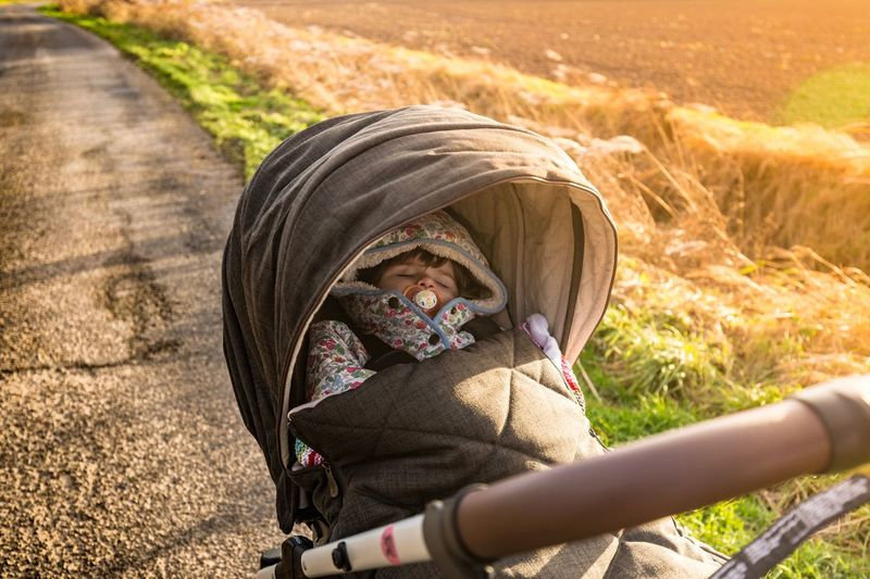 High Angle View Of Baby Sleeping In Stroller On Road By Field