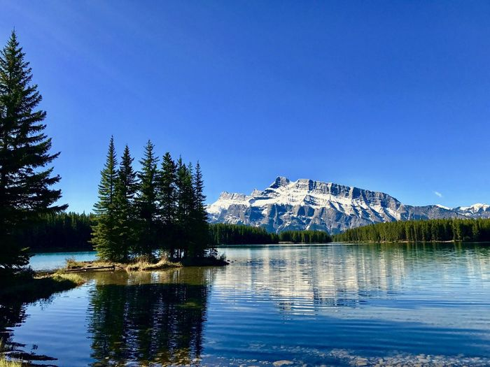 Scenic view of mt rundle by vermillion lakes against clear blue sky during winter