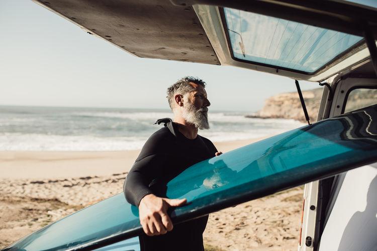 Side view of man keeping surfboard in car
