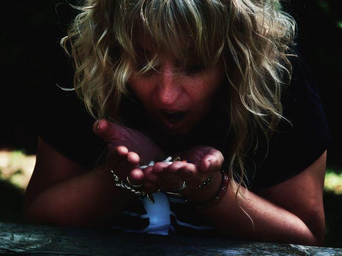 Woman holding pills outdoors