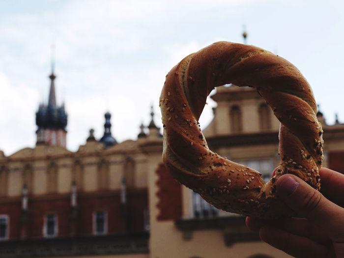 Close-up of hand holding pretzel against sky