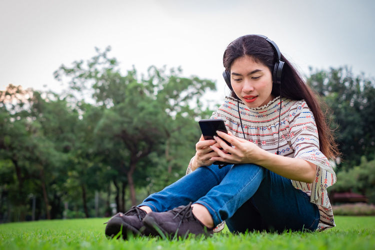 Woman listening music while sitting at park