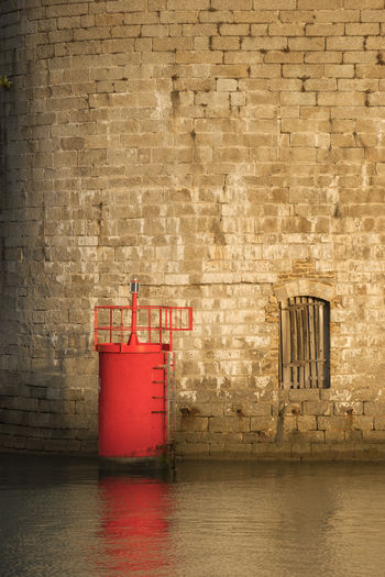 Red beacon on river against old building