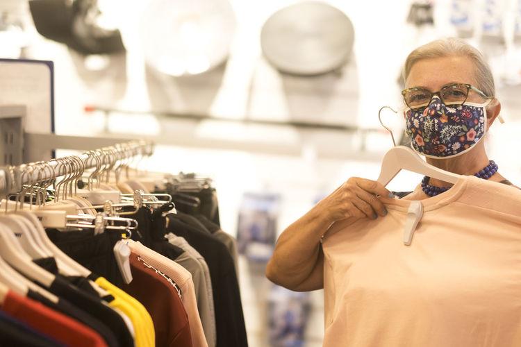 Senior woman buying dress in store