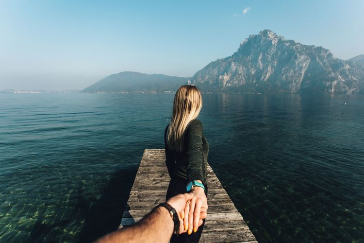 Water Mountain Beauty In Nature Lifestyles Real People Scenics - Nature Leisure Activity Nature Sky Women Adult Tranquil Scene Tranquility Non-urban Scene Hairstyle Long Hair Day Rear View Mountain Range Hair Outdoors Looking At View Couple Travel Destinations Hands