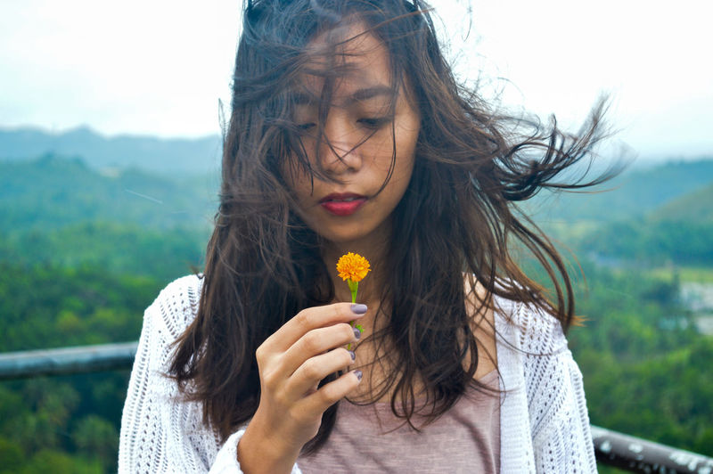 Young woman with tousled hair holding flower