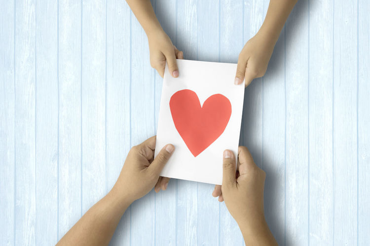 Cropped hands holding paper with heart shape on table