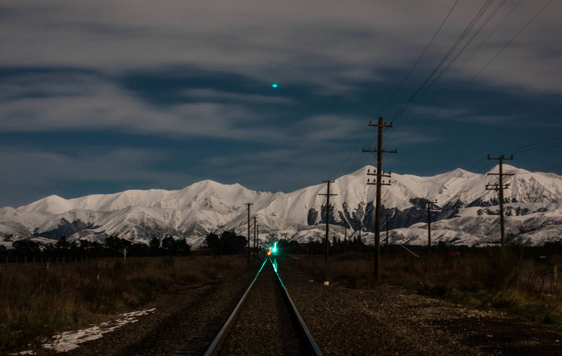 Snow covered mountains and railway track by moonlight Alps Beauty In Nature Cloud - Sky Diminishing Perspective Direction Environment Green Light Long Exposure Mountain Mountain Range Mountains Nature No People Outdoors Rail Transportation Railroad Railroad Track Railway Track Scenics - Nature Sky Snow Snowcapped Mountain Track Train Transportation