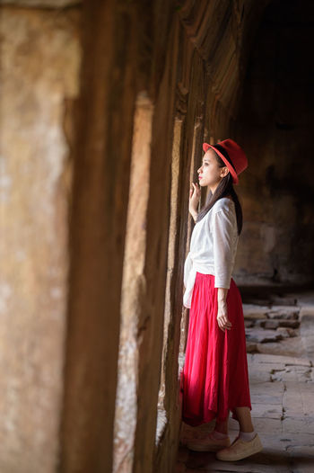 A young woman looks out of the window Adult Beauty Child Day Fashion Indoors  Monument One Person People Period Costume Portrait Red Traditional Clothing Women