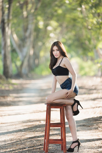 Portrait Of Seductive Young Woman On Stool In Forest