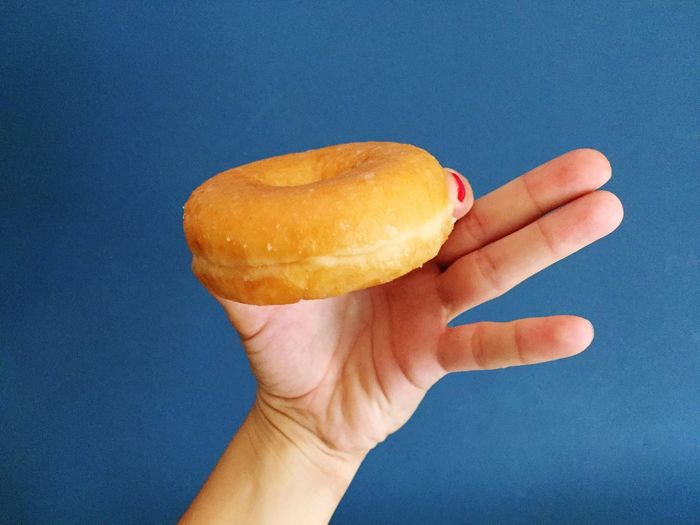 Cropped Hand Of Woman Holding Donut Against Blue Background