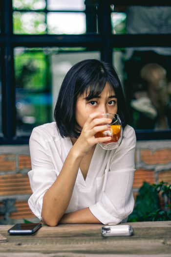 Portrait of woman drinking tea while sitting at cafe