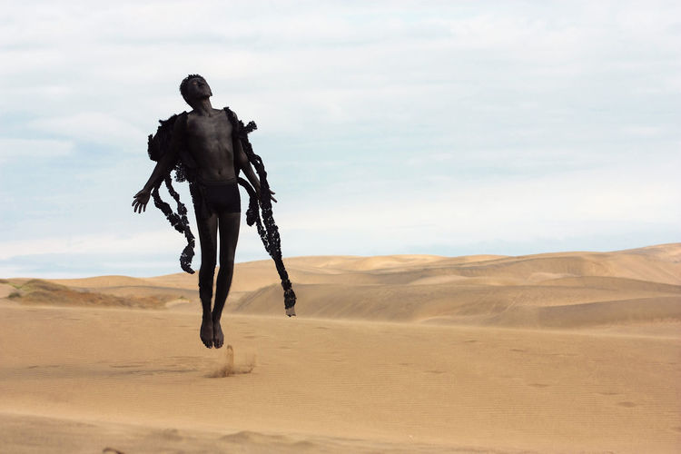 Young man in costume jumping at desert against sky