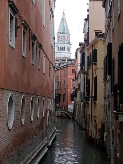San marco campanile seen from canal amidst buildings
