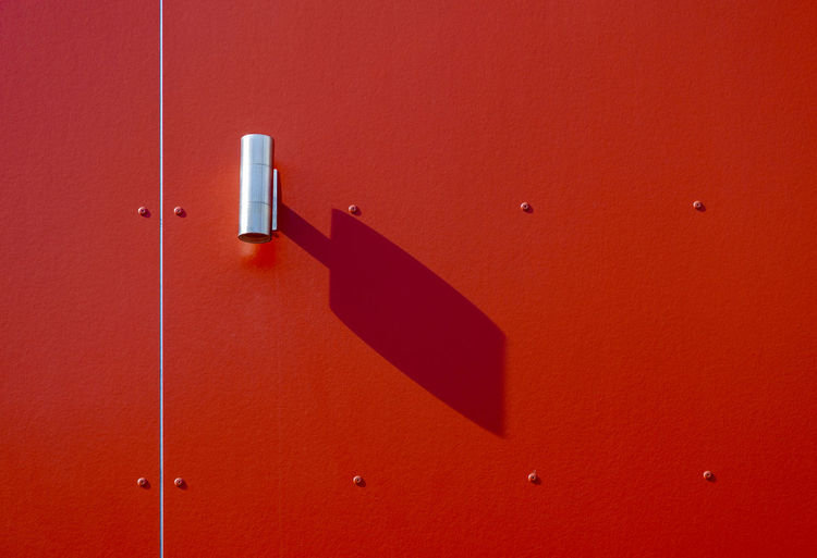 Modern outdoor light lamp with shadow on red wall on sunny day