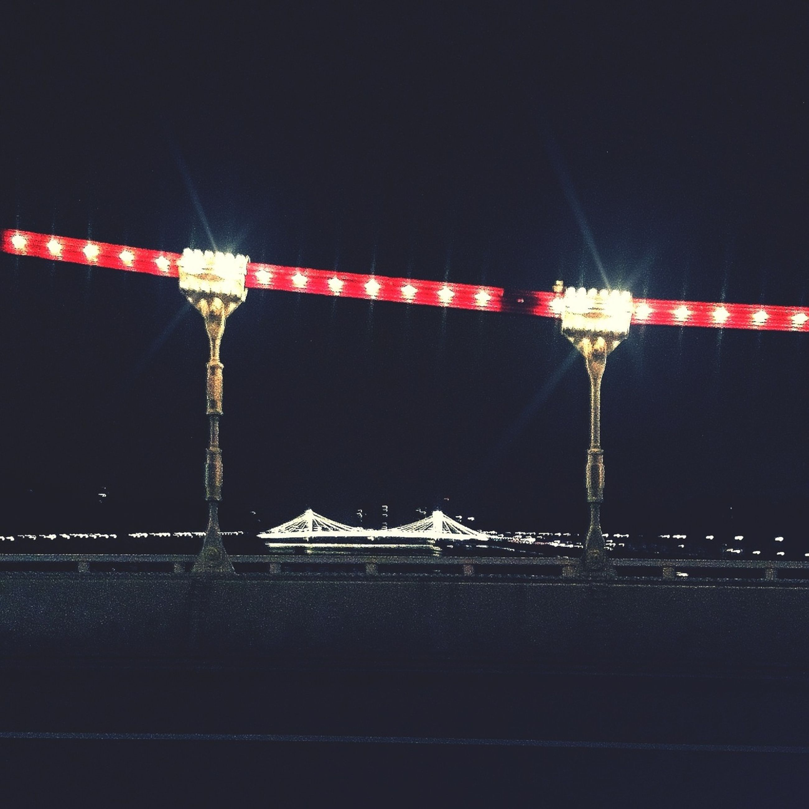 night, illuminated, copy space, lighting equipment, red, clear sky, multi colored, electricity, dark, low angle view, arts culture and entertainment, outdoors, street light, no people, long exposure, hanging, built structure, in a row, electric light, motion