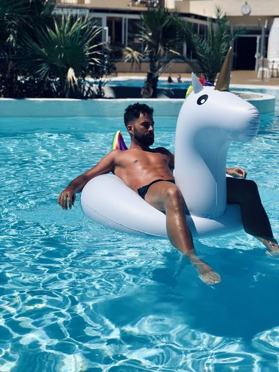 Man sitting on pool raft at swimming pool