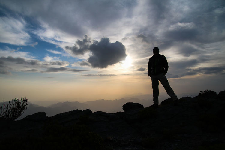 Rear view of man standing on mountain landscape against sky