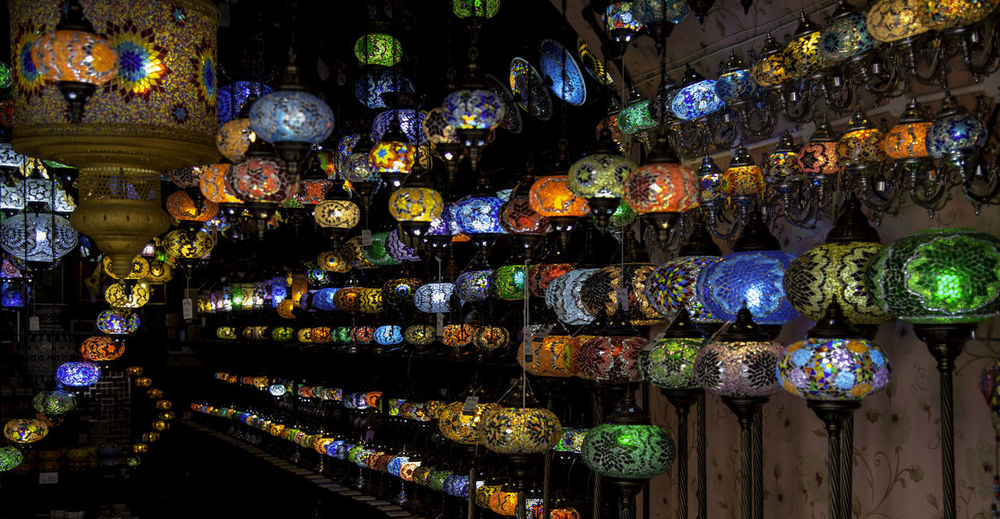 Multi colored lanterns hanging in shelf at market stall