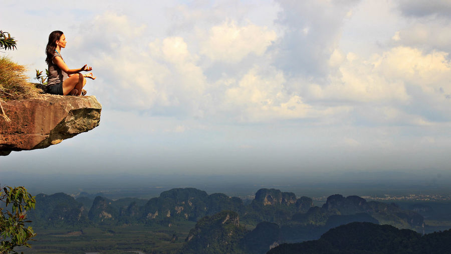 Woman Meditating On Cliff Against Cloudy Sky