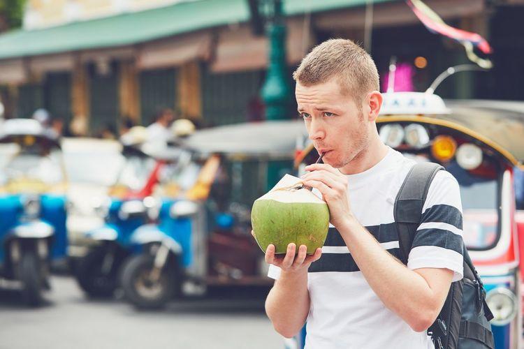 Man drinking coconut water on street