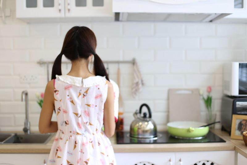 Rear View Of Young Woman Preparing Food In Kitchen