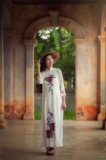 Woman dressed Vietnamese Vietnamese Arch Architectural Column Architecture Building Exterior Built Structure Day Dressed Front View Full Length Happiness Indoors  Leisure Activity Lifestyles One Person Real People Standing Traditional Clothing Young Adult Young Women