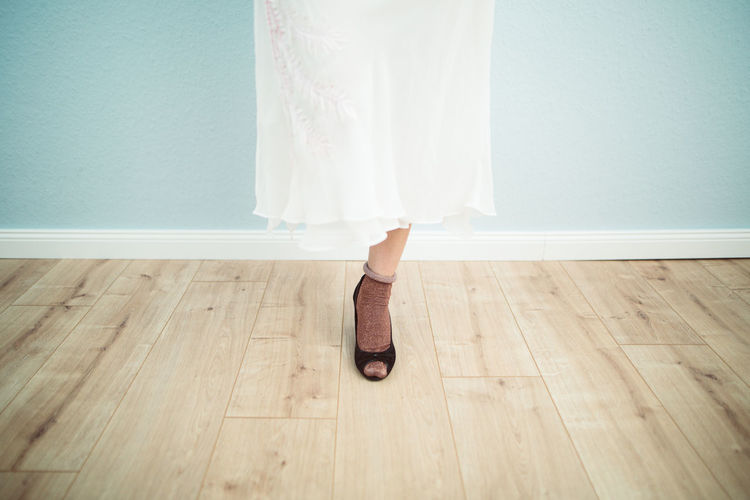 Low section of woman wearing high heels while standing on hardwood floor