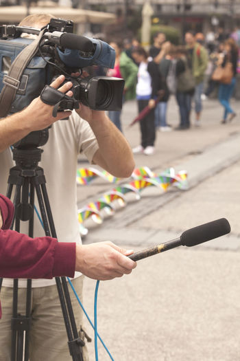 Cameraman with reporter taking interview at street