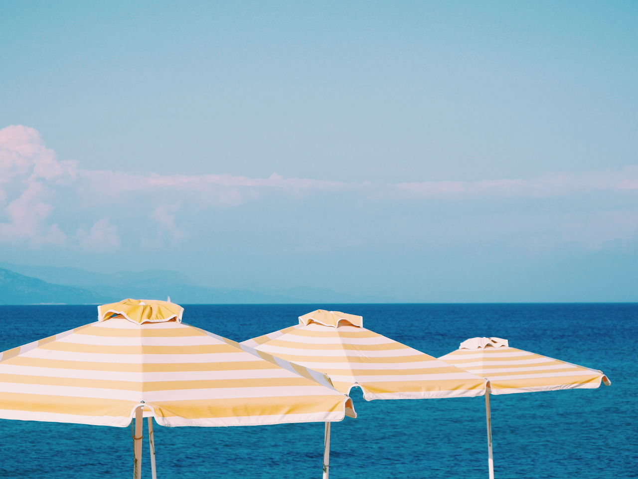 sea, water, beach, horizon over water, beach umbrella, beauty in nature, scenics, shore, nature, protection, summer, tranquility, sand, sky, tranquil scene, canopy, outdoors, no people, vacations, sun lounger, day, shelter, cloud - sky