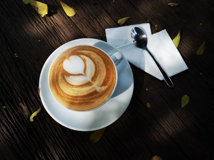 coffee latte art on wooden table Coffee Cafe Time Coffee Cup Froth Art Cappuccino Frothy Drink Drink Latte Directly Above Table Coffee - Drink High Angle View Coffee Cup Autumn Mood